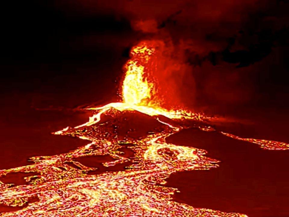 Lava tyter ut av en vulkan og renner nedover.