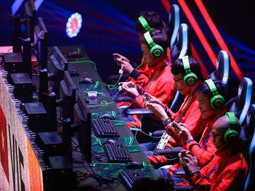 Fem gutter med røde jakker og grønne headset, sitter på rekke og spiller.
