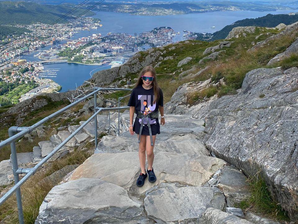 En jente med shorts og raske briller går opp steintrapper med utsikt over gondolbanen til Ulriken, med Bergen by og sjøen i bakgrunnen.