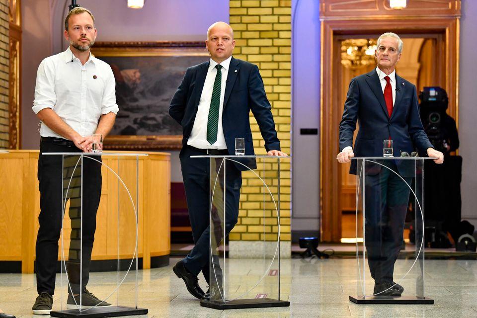 Tre menn i penklær står bak hvert sitt høye glassbord.