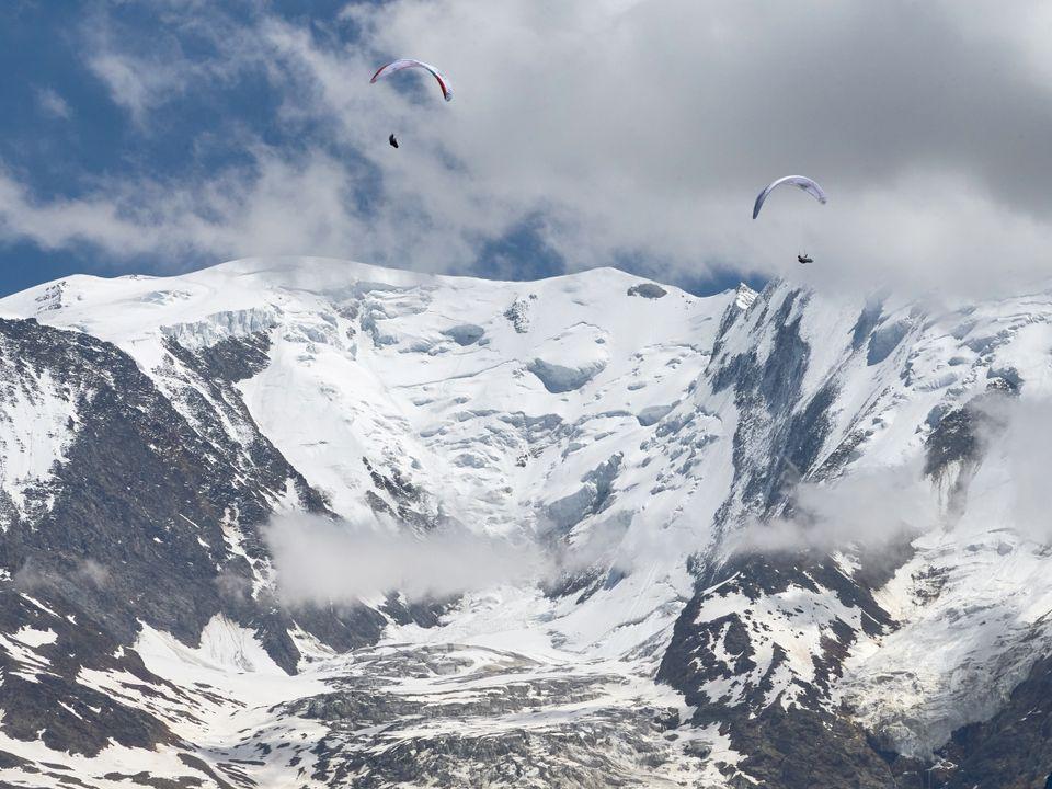 To paraglidere seiler på en blå himmel med isdekkene Mont Blanc i bakgrunnen.