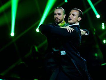 To menn i dress holder hverandre på skuldrene i en tango mens de ser dramatisk fremover.