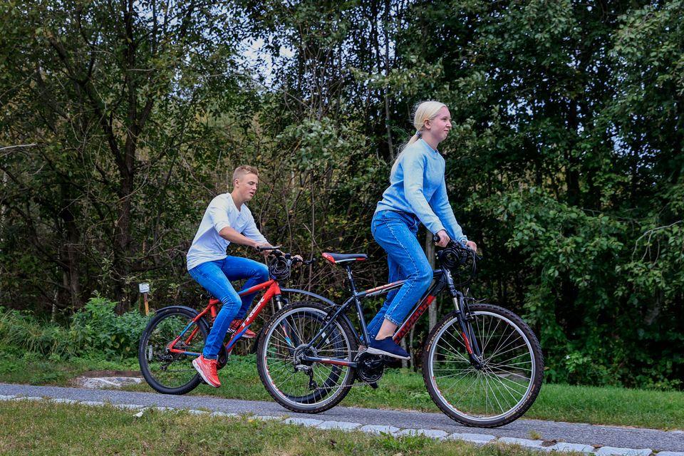 En jente i blå genser som sykler på en sort sykkel foran en gutt i hvit t-skjorte på rød sykkel.