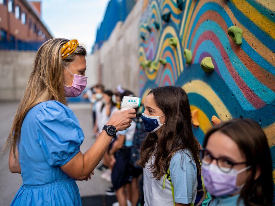 En lærer med langt hår, munnbind og blå kjole scanner temperaturen i pannen til en rekke med elever som står foran en klatrevegg.