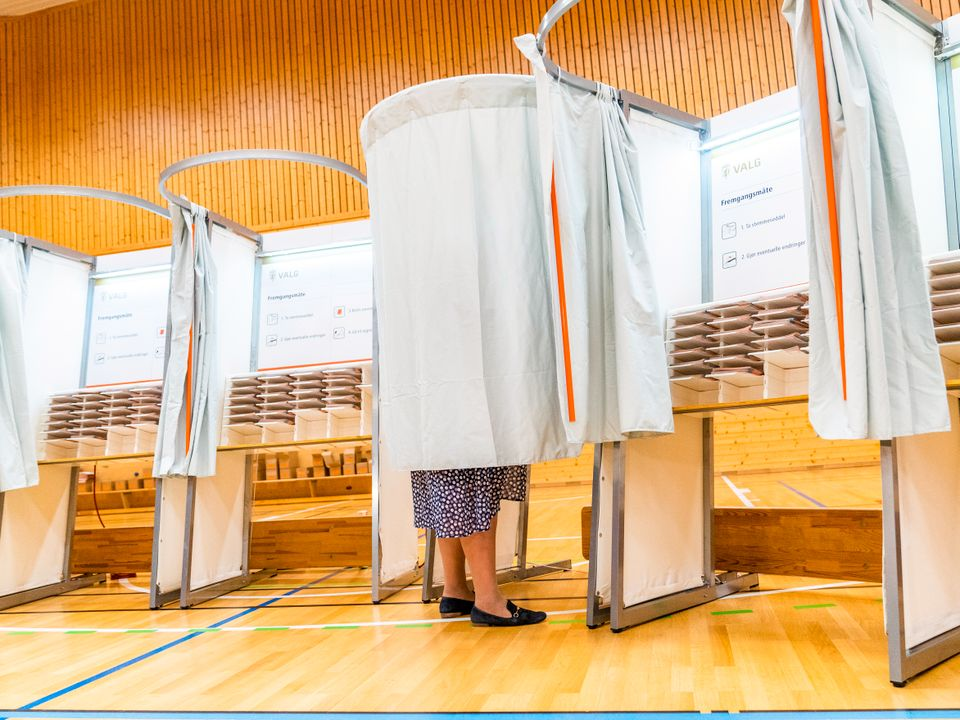 Beina til en person med skjørt og sorte sko synes under forhenget på et valgavlukke, inne i et rom på Skjold skole i Bergen.