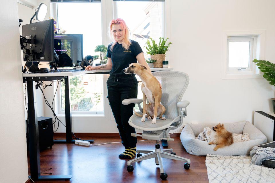 Nora Helen Engelsvold står ved dataskjermen sammen med en hund og en katt.