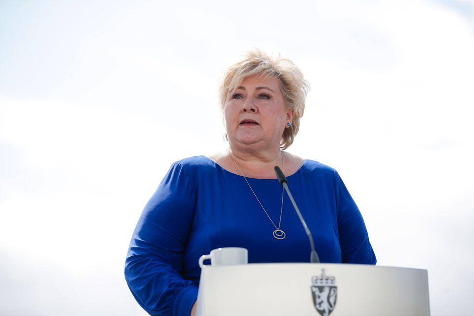 Erna Solberg står på talerstolen og snakker i en mørkeblå kjole.