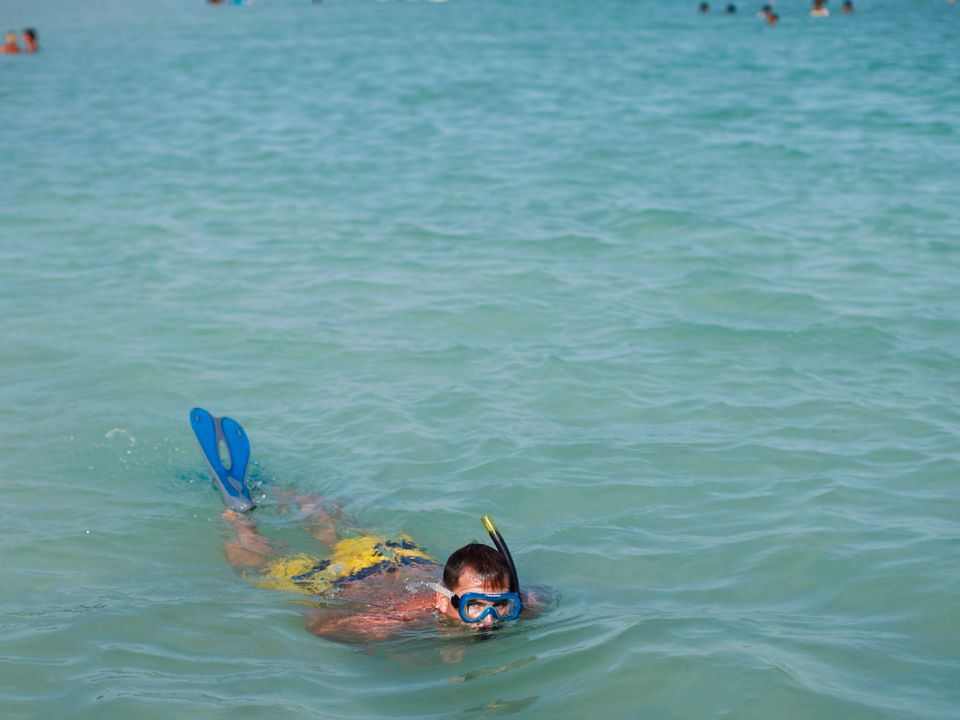 En mann med badeshorts, snorkel og svømmeføtter svømmer i turkist, rolig vann mens han kikker opp på fotografen.