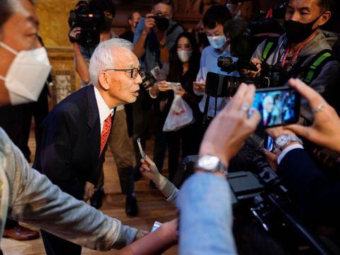 En mann med hvitt hår og briller lener seg frem mot en mengde med reportere.