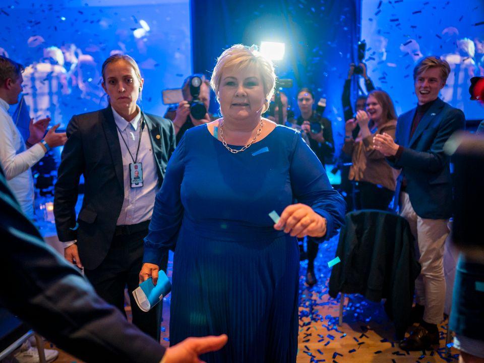 Erna Solberg har på seg en blå kjole og går mot fotografen, på vei ut av den blåpyntede valgvaken til Høyre.