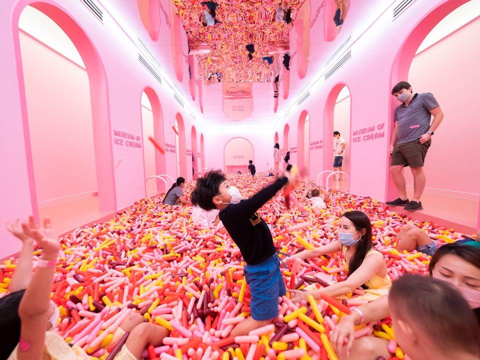 Barn leker i et knallrosa type ballrom hvor gulvet er fylt med objekter som likner fargerikt tuttifrutti-strøssel.