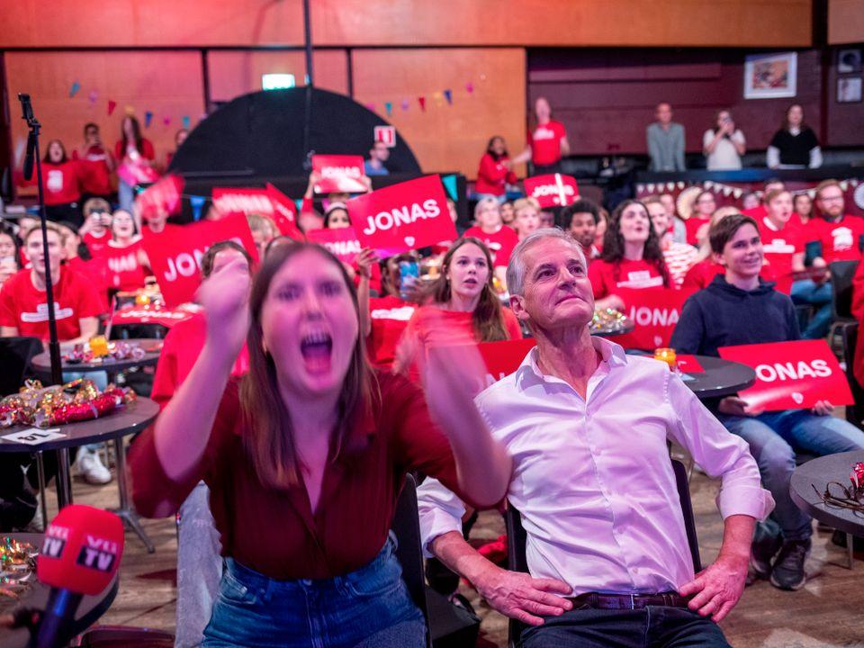 """Jonas Gahr Støre sitter bakoverlent på en stol, ikledd skjorte, mens et rom fullt av rødkledde Ap-medlemmer jubler og løfter røde skilt med navnet """"Jonas"""" på."""