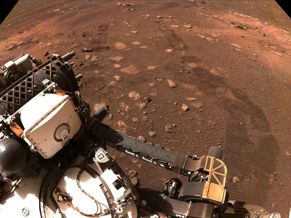 En hvit robot etterlater seg spor i den oransje bakken på Mars.