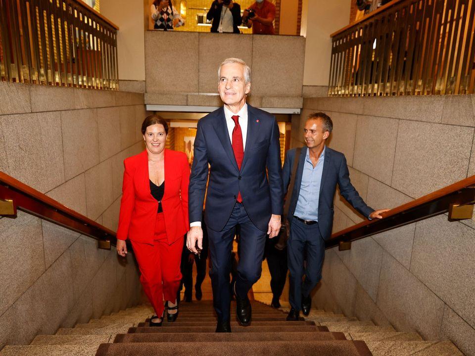 Jonas Gahr Støre går opp trappene inni Stortinget, ikledd dress og rødt slips, med medierådgiveren og en kvinne i rød dress like bak.