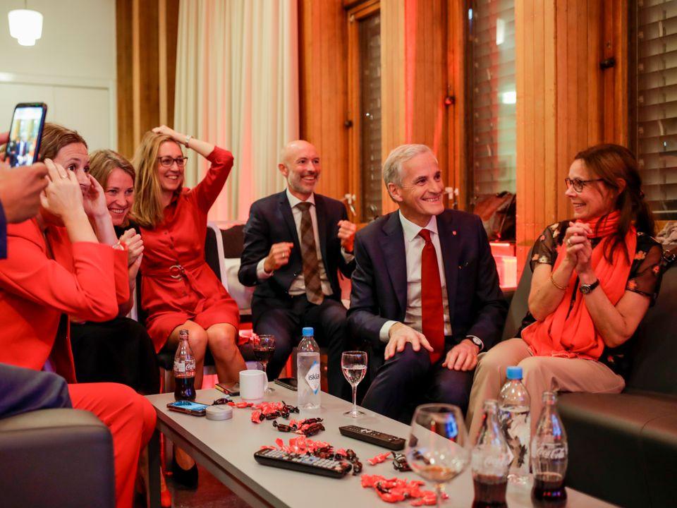 Støre, med rødt slips, og en gruppe støttespillere sitter rundt et bord og smiler og jubler, mens de antakelig ser mot en skjerm eller person som deler foreløpige resultater fra opptellingen.