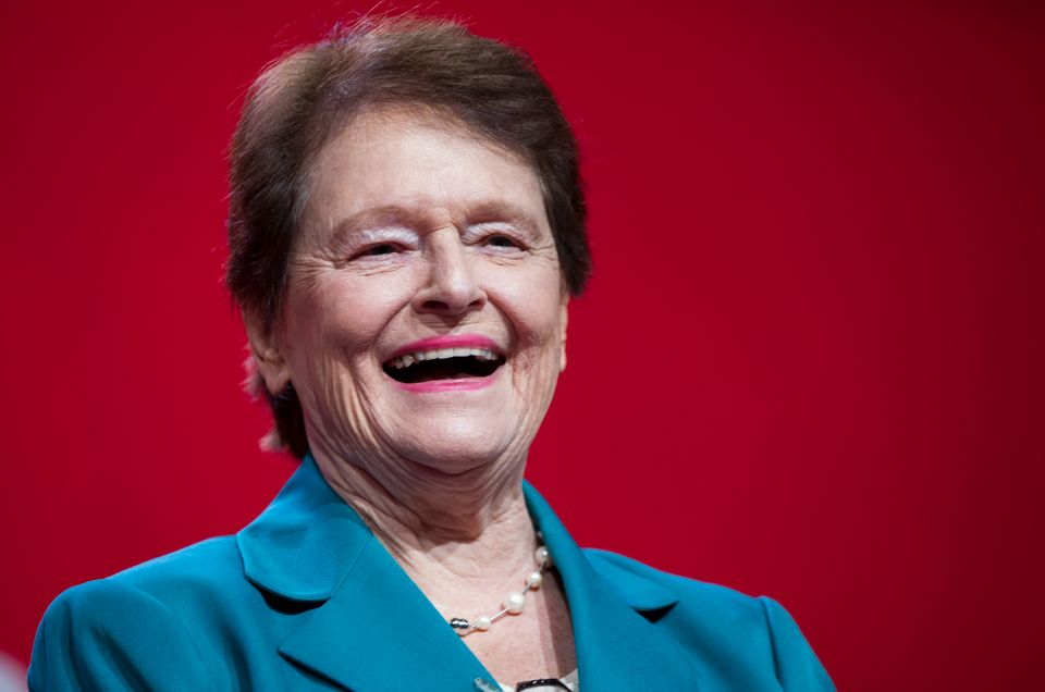 En eldre dame med brunt hår og rosa leppestift ler og smiler.