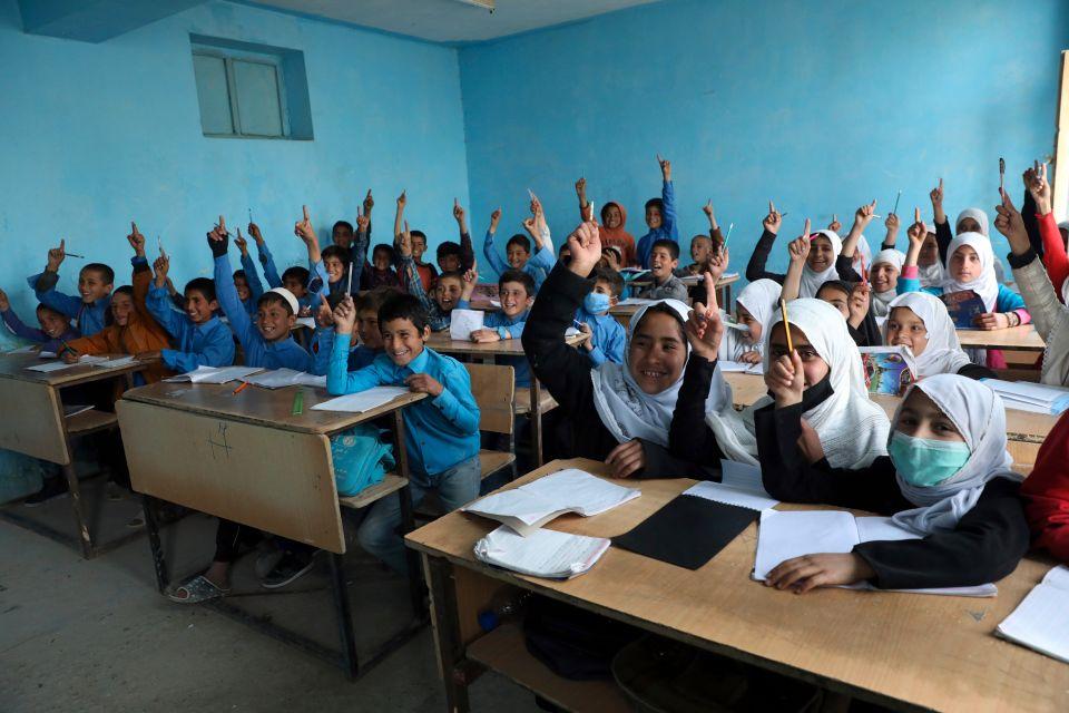Mange afghanske barn i et klasserom. Flere av dem rekker opp hånden og vil svare på et spørsmål.