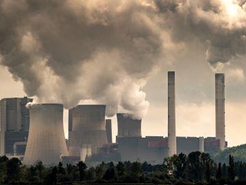 Masse grå røyk stiger opp fra pipene på et fabrikkbygg.