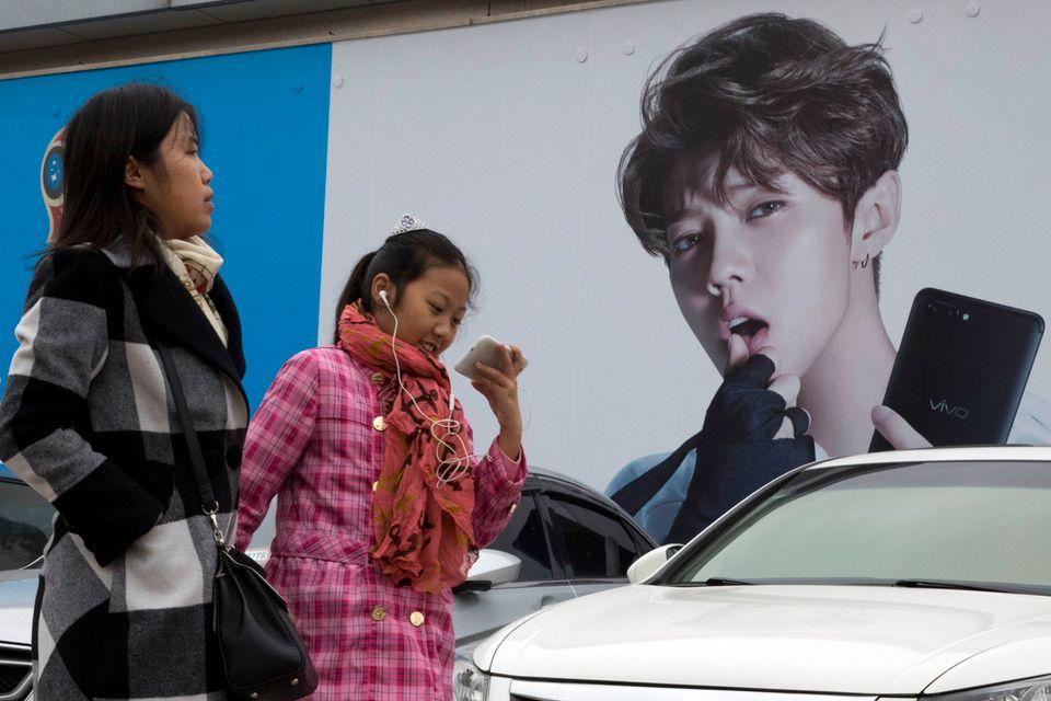 To kinesiske kvinner går forbi en stor plakat av den kinesiske sangstjernen Lu Han.
