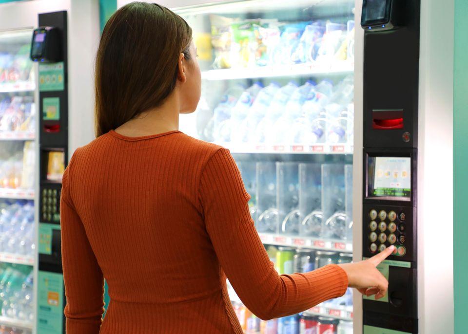 En jente i rødbrun genser trykker på knappene på en brusautomat