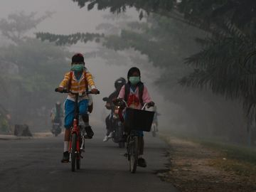 To jenter med munnbind sykler til skolen i forurenset luft.