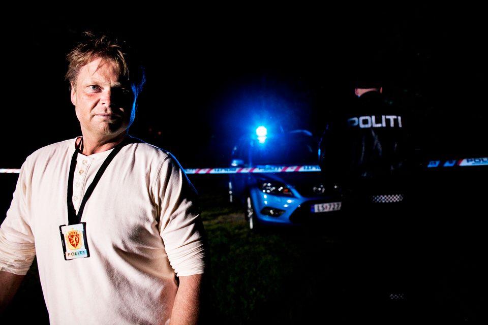 Halvnært portrett av Horst, med politi-id hengende rundt halsen og et blålys, åstedsteip og en politimann i den mørke bakgrunnen.