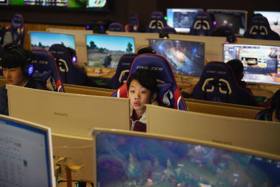 En kinesisk gutt sitter mellom mange PC-skjermer på et gaming-arrangement og spiller.