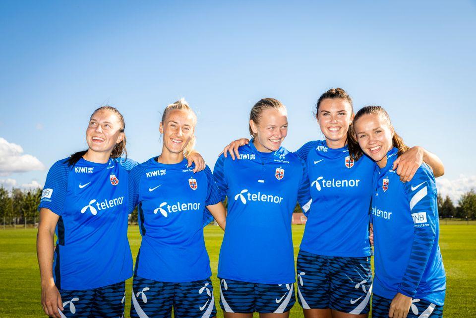 Fem blide norske landslagsspillere smiler på trening.