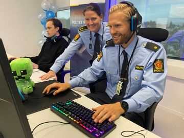To menn og en kvinne i lyseblå politiuniformer sitter foran PC-skjermer og trykker på tastaturene.