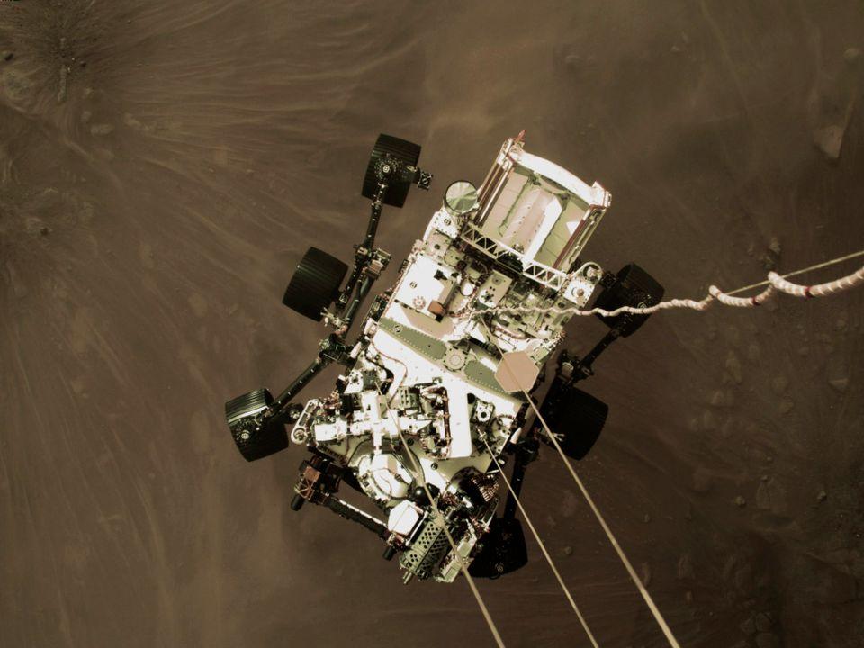 Den hvite roboten Perseverance har mange hjul og masse utstyr festet på seg.
