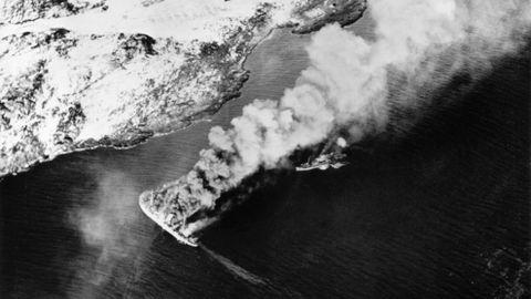 MS Rigel blir raskt oppdaget etter å ha forsøkt å forflytte seg da dagen er på sitt lyseste. Skipet blir truffet av lufttorpedoer og er i ferd med å synke. | En av de militære følgeskipene forsøker å komme til for å berge overlevende.