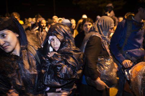STORM: Regnet pøser ned på Oruba Azzam (6), mens hun venter på å krysse grensen fra Hellas til Makedonia like før midnatt fredag. Tanten Shamo bærer henne på armen. - Når kan vi slippe gjennom? spør hun. Vi har ikke noe svar.