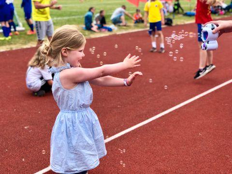 BOBLER AV GLEDE: Mens noen jakter ball på gressmatten, jakter Josephine (4) såpebobler på sidelinjen. Hun er med storebroren som spiller for Sotra SK på Voss cup.