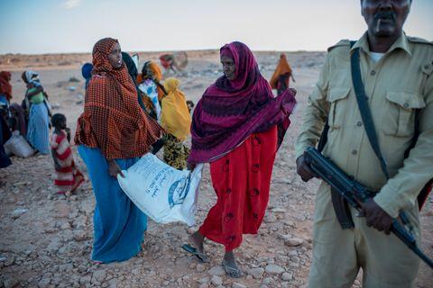 SULT: Kvinner med mat fra Kirkens Nødhjelps utdeling i Somalia. Da Håvard Bjelland fotograferte for hjelpeorganisasjonen i Etiopia for et år siden kokte mødre blader for å gi barna et eller annet å fylle magen med. Her er ingen blader å koke. Alt er avsvidd.