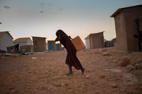REDNING: En ung jente er på vei hjem med rent vann.
