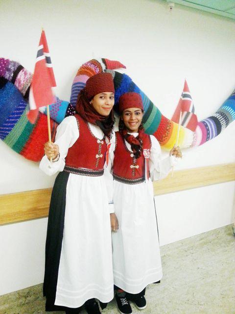 JA, VI ELSKER: En anonym giver overrasker Zahra og Shou-Shou med norske festdrakter til 17. mai. Sammen med sykepleierne øver de på «Ja, vi elsker» foran speilet. FOTO: PRIVAT