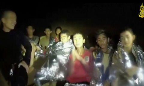 MAT OG TEPPER: Dette bildet viser guttene sammen med marinesoldater dagen etter at de ble funnet. Guttene fikk mat og folietepper som gir lavere varmetap.