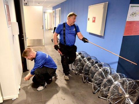 FRA VENSTRE: Dan Erik Hammersland og Ove Hesvik fra skadealliansen begynner å rive deler av fuktskadde gipsvegger på Osterøy vgs.