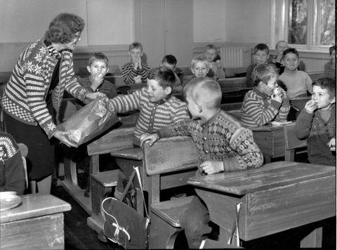 FANAJAKKE: I november 1958 delte «frøken» ut epler til elevene, i forbindelse med en kampanje for frukt og sunn mat. Det var elever ved Nordnes og Rothaugen skoler som fikk gratis frukt og en brosjyre med hjem om hvor viktig frukt var for tennene.