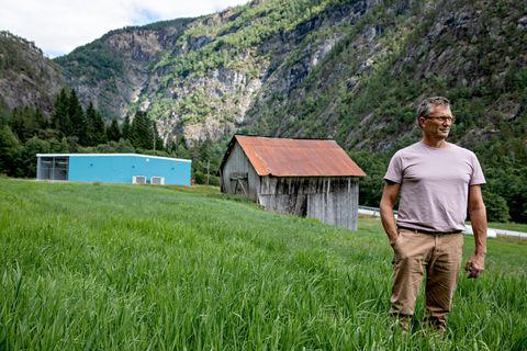 ÅPNER FOR BITCOIN: Daglig leder Edvin Brun i datasenteret Bluefjords i Luster med det turkise datasenteret i bakgrunnen. Han håper hele den grønne engen kan fylles med flere datasentre de neste årene.