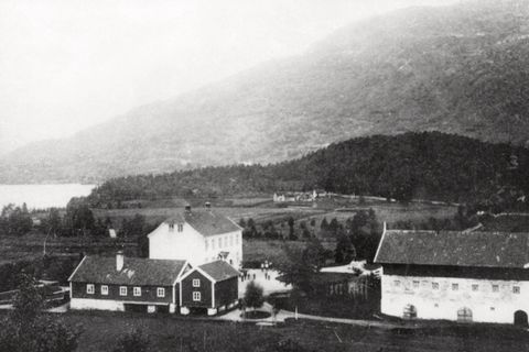 BARNDOM: Jordbruksskulen på Mo i 1891. I husklyngja i bakgrunnen ligg Teigen. Dette er det einaste fotografiet som finst av husmannsplassen, der Inger Oline vaks opp.