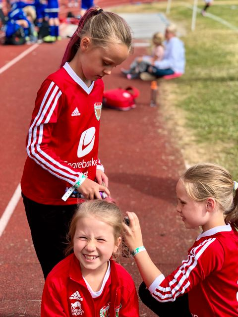«REGNBUEHÅR»: Kristine (9) får håret sprayet av bursdagsbarnet Lotta (9) (til venstre) og Ella (9). De spiller for Loddefjord Lilla, til tross for sine røde drakter.