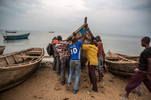 ETTER ANKOMST: En gruppe menn flytter en av båtene som ankom tidligere den samme morgenen.