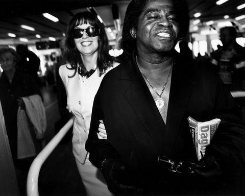 31. MAI 1996: James Brown seiler gjennom ankomsthallen på Flesland, i selskap med Deanna Ares. At funklegenden bærer på Dagbladet, kan være fordi avisen denne dagen har brukt fem sider på hans norgesbesøk. FOTO: EIRIK BREKKE