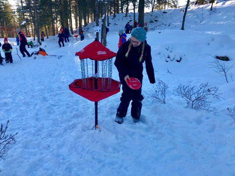 SNØ-FRISBEE: Turistforeningen arrangerte flere aktiviteter, blant annet snø-frisbee. – Vi må treffe opp i kurven, forklarer Maja (13).