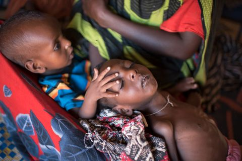 TRØSTENDE HÅND: Lillebror Ahmed (9 måneder) legger en trøstende hånd på storesøster Farhiya Rihman Abdulahy. Hun er to og et halvt år, men har vekten til en baby. Syk av sult ligger hun i fanget på mamma Buha, som har mistet to andre barn de siste månedene. Nå får hun hjelp, livreddende mat og drikke til sine to små i Uusgure, en liten landsby av telt i ørkenen. Fotograf Håvard Bjelland hører mødre fortelle at de om ikke annet må bort fra ørkenen og inn hit til landsbyen, slik at barna slipper å dø alene.