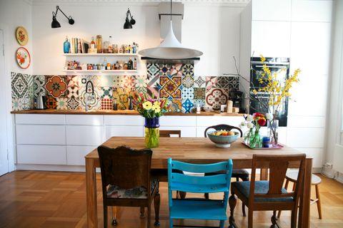 Ulike fargerike fliser pryder kjøkkenveggen og lager en eksotisk stemning i leilighetens selvskrevne hjerte. Kjøkkenet er nytt, men kjøkkenhyllene har Steinar laget av de gamle gulvplankene som lå i gangen.